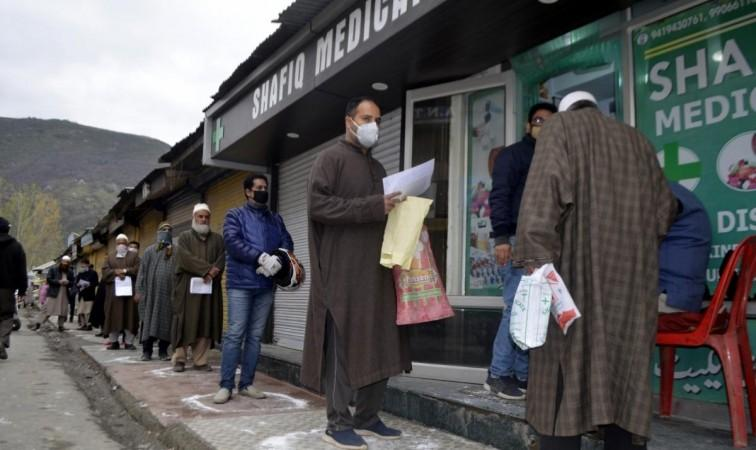 Baramulla: Menschen, die während der 21-tägigen landesweiten Sperrung, die als Vorsichtsmaßnahme zur Eindämmung der Verbreitung von COVID-19 in Jammu und Kashmirs Baramu verhängt wurde, strikt soziale Distanzierung praktizieren, während sie sich anstellen, um Medikamente außerhalb eines medizinischen Geschäfts zu kaufen