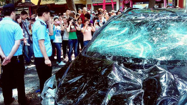 Menschen machen Fotos von einem japanischen Auto, das bei einem Protest gegen die Verstaatlichung Japans beschädigt wurde. der umstrittenen Diaoyu-Inseln, in Japan auch als Senkaku-Inseln bekannt, in der chinesischen Stadt Xi am 15. September 2012.