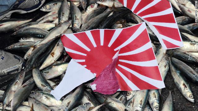 Eine auseinandergerissene japanische & # 39; Rising Sun & # 39; Während einer Demonstration in Taipeh am 14. September 2010 über der umstrittenen Inselkette Senkaku / Diaoyu wird auf toten Fischen eine Flagge angebracht.