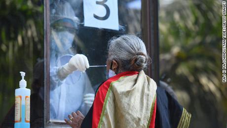 Ein Sanitäter sammelt einen Tupfer von einer Frau, um am 18. Juni in Neu-Delhi, Indien, auf Covid-19 zu testen.