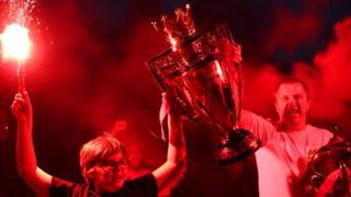 Zwei Liverpool-Fans feiern mit einer Replik der Premier League-Trophäe außerhalb von Anfield