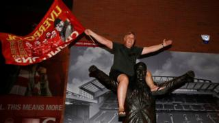 Ein Liverpool-Fan feiert den Gewinn der Premier League, als er auf einer Statue von Bill Shankly außerhalb von Anfield sitzt