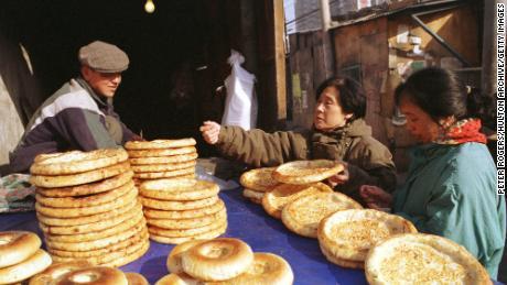 Ein uigurischer Mann verkauft 1999 traditionelles Fladenbrot an Käuferinnen in der Xinjiang-Straße in Peking.