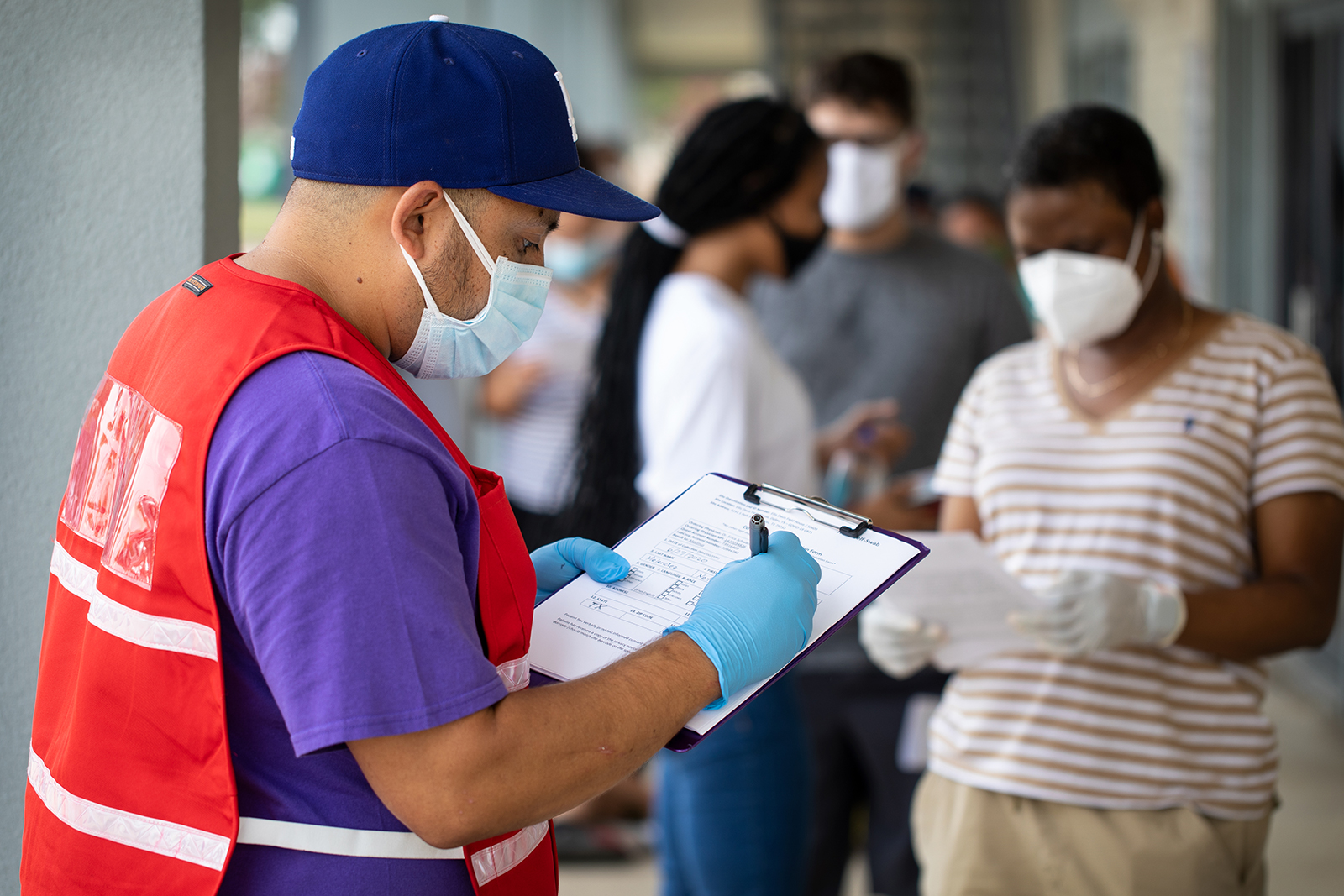 Community outreach specialist Rogelio Bucio collects patient information as they wait in line at a walk up Covid-19 testing site on June 27, in Dallas, Texas.