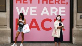 Zwei Personen mit Gesichtsmasken vor dem Laden