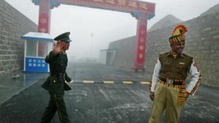 Ein chinesischer Soldat und ein indischer Soldat bewachen 2008 die chinesische Seite des alten Grenzübergangs Nathu La zwischen Indien und China