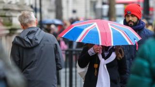 Eine Frau schützt vor dem Regen unter einem Union Jack-Regenschirm während des Regens im Zentrum von London.