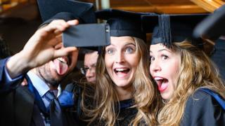 Studenten, die nach dem Abschluss für ein Foto posieren