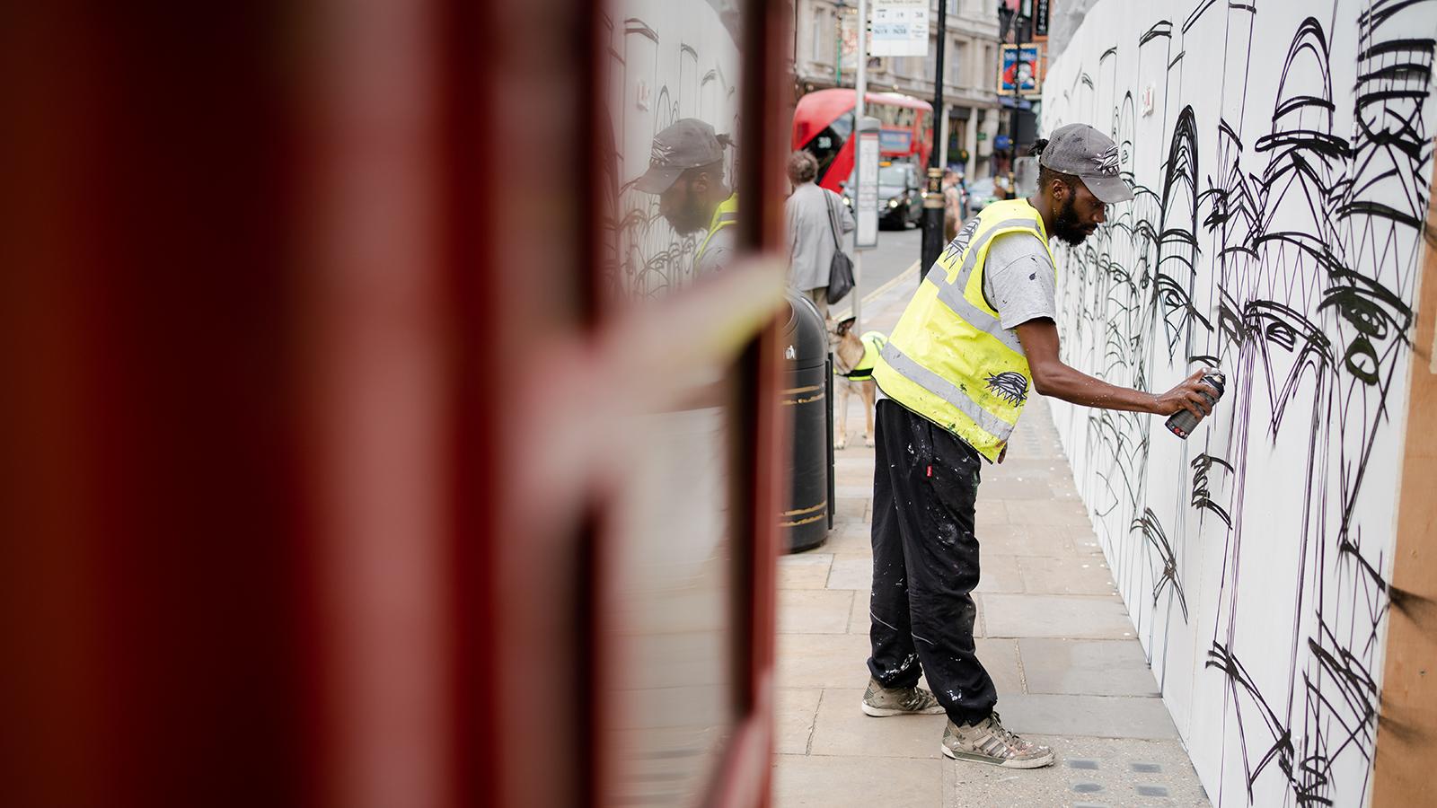 Der Straßenkünstler Nathan Bowen arbeitet am Freitag in London an einem Bild.