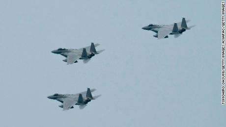 Japans F-15-Kampfflugzeuge der Air Self-Defense Force fliegen während einer Überprüfung nach der Abschlussfeier der Nationalen Verteidigungsakademie am 22. März 2020 in Yokosuka, Japan.