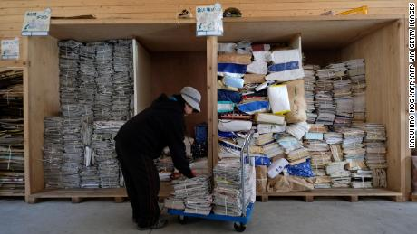 Ein Arbeiter sortiert Zeitungen und Zeitschriften zum Recycling in einem Abfallzentrum in Kamikatsu.