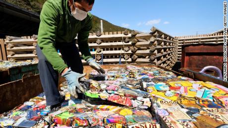 Ein Bewohner stapelt Blätter mit verdichteten Aluminiumdosen in einem Abfallzentrum in Kamikatsu, Präfektur Tokushima.
