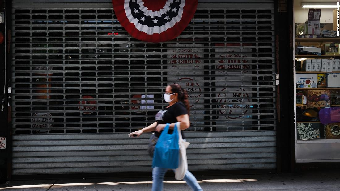 People walk by stores, many closed, along River Avenue near Yankee Stadium on July 23, 2020 in the Bronx borough of New York City. Yankee stadium, which is closed to fans due to COVID-19 and social distancing restrictions, was a magnet for traffic to businesses in the area surrounding the famed stadium and many now stand closed or operate on restricted hours. The area of the South Bronx adjacent to the stadium has an unemployment rate of over 21 percent and is one of the country's poorest congressional districts. Major League Baseball will start up tonight to stadiums empty of fans. (Photo by Spencer Platt/Getty Images)