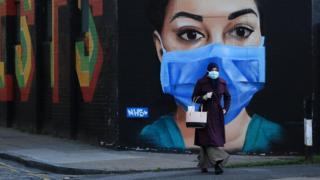 Eine Frau mit Maske geht vor ein Wandbild eines NHS-Arbeiters