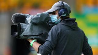 Ein Kameramann trägt eine Gesichtsmaske, während er bei einem Fußballspiel in Norwich filmt