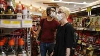 Käufer, die am 11. Juli 2020 in Islington Gesichtsmasken tragen