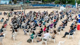 Das Publikum hält während einer Aufführung an einem Strand in A Coruna, Spanien, am 4. Juli soziale Distanz aufrecht