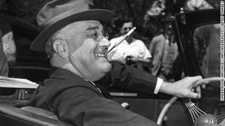 Mit einer Zigarette in einer zusammengebissenen Halterung sitzt ein lächelnder Franklin Delano Roosevelt unbeschwert am Steuer seines Cabriolets Warm Springs, Georgia, 1939. (Foto von Underwood Archives / Getty Images)