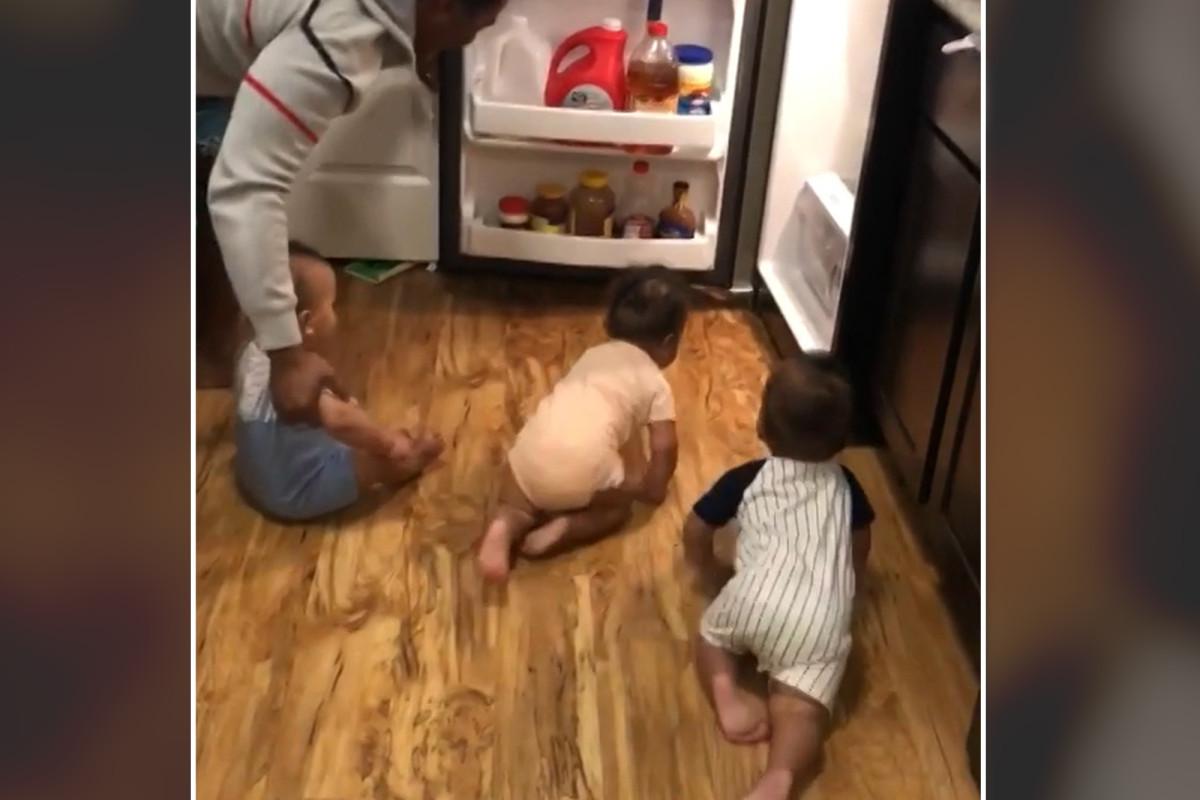 Papa kämpft darum, Drillinge zu streiten, die in einem lustigen Video den Kühlschrank überfallen