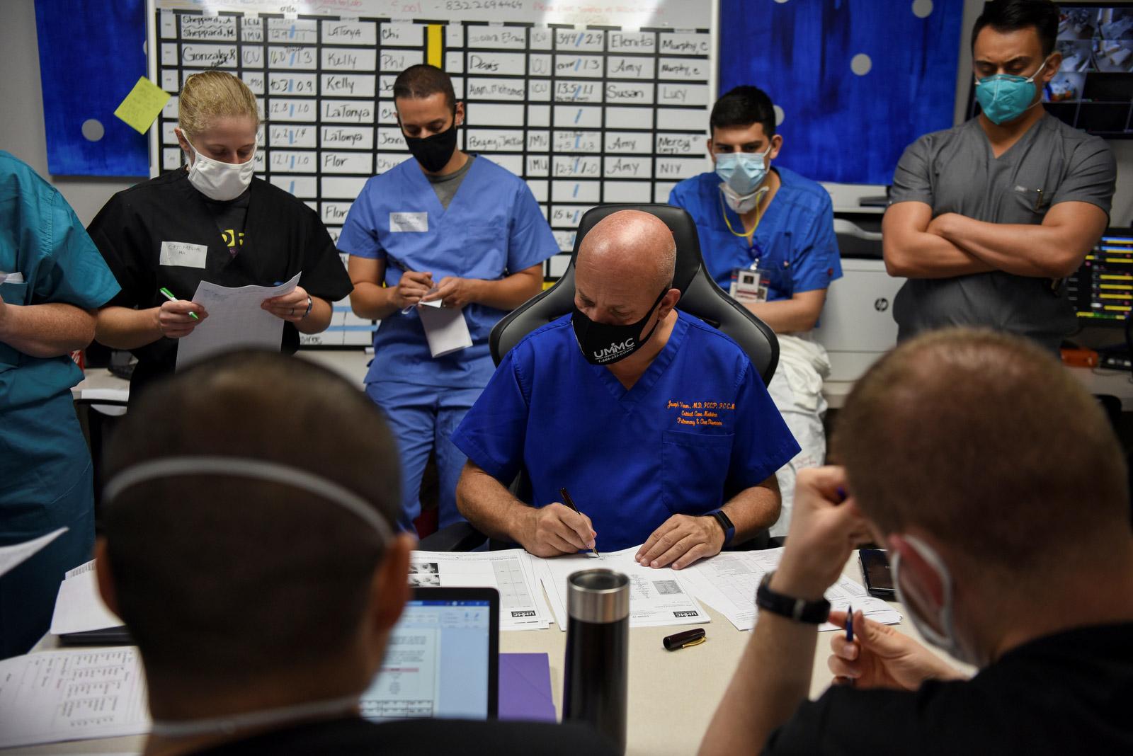 Varon und sein Team gehen während eines täglichen Meetings die Patientenakten durch.
