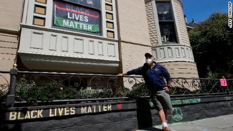 James Juanillo posiert mit einer Kreidebotschaft, die am 14. Juni 2020 außerhalb seines Hauses in San Francisco, Kalifornien, geschrieben wurde.