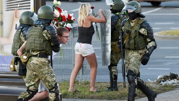 Eine Frau in einem Streit mit einem Polizisten: Frauen werden immer wieder mit Sicherheitskräften konfrontiert - wenn möglich mit Umarmungen.  (Quelle: AP / dpa)