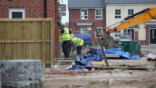 Bauarbeiter bauen neue Häuser auf einer Wohnsiedlung in England