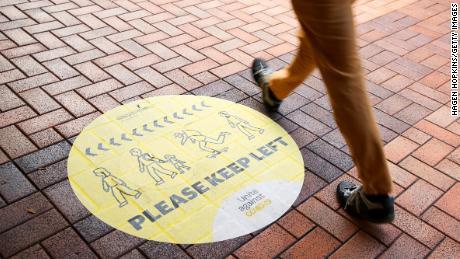 Ein Fußgänger geht am 14. August 2020 in Wellington, Neuseeland, an einem sozialen Distanzierungsschild vorbei.