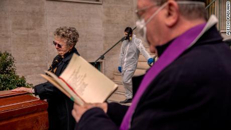 Ein Priester, der eine Maske trägt, segnet am 27. März einen Sarg im Hof eines Gebäudes in Neapel, Italien.